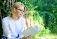 Literature as hobby. Girl keen on book keep reading. Bestseller top list concept. Woman blonde take break relaxing in. Park reading book. Girl relaxing with royalty free stock image