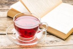 Literature background. Cup of hot tea with opened book. On wooden table Stock Image