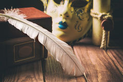 Literature concept. Feather on book near venetian mask and old scroll on wooden background.  Royalty Free Stock Photo