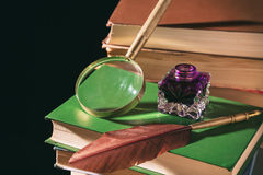 Literature concept. Inkstand with feather near magnifying glass on old books against black background.  Stock Photo