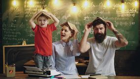 Literature concept. Little child boy and parents with books on their heads, literature. School boy study literature in. Classroom. Literature is my hobby stock footage