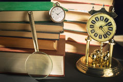 Literature concept. Magnifying glass near vintage clocks and old books against black background. Royalty Free Stock Photography