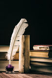 Literature concept. Old inkstand with feather near scroll and books on black background Royalty Free Stock Photo