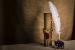 Literature concept. Old inkstand with feather near scroll and on canvas background Stock Photo