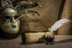 Literature concept. Old inkstand with feather near scroll and venezian mask on canvas background Stock Image