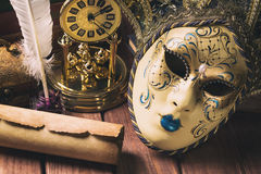 Literature concept. Still life with feather in inkstand, scroll, venetian mask, old books,vintage clock and box on wooden table. V Stock Image