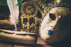 Literature concept. Still life with feather in inkstand, scroll, venetian mask, old books,vintage clock and box on wooden table. V Royalty Free Stock Photography