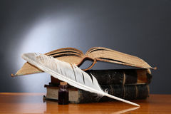 Literature Concept. Still life with quill pen near book on wooden table Royalty Free Stock Image