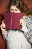 Literature on the couch. Young woman reads a book lying on a couch Royalty Free Stock Image