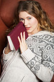 Literature on the couch. Young woman reads a book lying on a couch Stock Photography