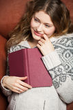 Literature on the couch. Young woman reads a book lying on a couch Royalty Free Stock Photos