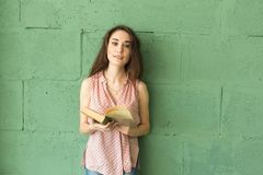 Literature, education, people concept - Female student in reading the book over the green wall.  stock photos