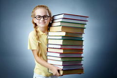 Literature girl. Image of happy schoolgirl with stack of books looking at camera Stock Photography