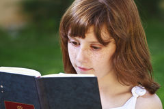 Literature.Young beautiful girl reading a book outdoor Royalty Free Stock Images