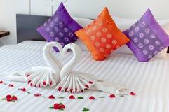 Literie d'hôtel avec l'origami de cygne Photographie stock