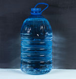5 liters. Big plastic bottle of potable water on a dark backgrou. 5 liters. Big plastic bottle of potable water, barrel with handle on a dark background Stock Image