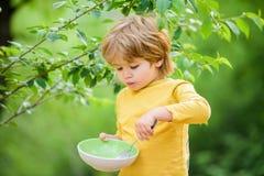 Litet äta för pojke som är utomhus- Barns utveckling Pysen äter sund mat Barndomlycka Sund mat och banta royaltyfria bilder