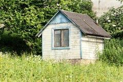 Litet övergett vitt trädgårdhus med det enkla fönstret royaltyfri foto