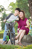 Litet asiatiskt barn med moderövning till att rida en cykel arkivbild