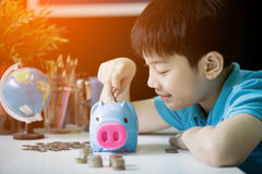 Litet asiatiskt pojkemellanläggsmynt in i spargrisen Royaltyfria Foton