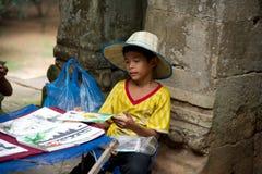 Litet asiatiskt pojkesammanträde med några till salu souvenir Fotografering för Bildbyråer
