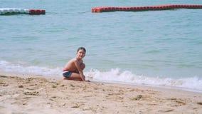 Litet asiatiskt pojkesammanträde på sand på den Pattaya stranden lager videofilmer