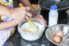 Litet asiatiskt vetemjöl och ägg för flicka och för moder blandande som gör pannkakan Royaltyfria Bilder