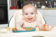Litet b som äter hennes matställe och gör en röra royaltyfri bild