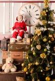 Litet barn i den santa dräkten på julträdet royaltyfria bilder