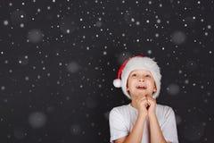 Litet barn i den Sante hatten som drömmer av de magiska julgåvorna Royaltyfri Bild