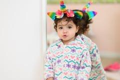 Litet barn i Unicorn Costume fotografering för bildbyråer