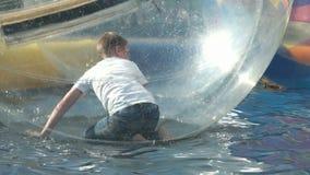 Litet barn inom en stor uppblåsbar boll i vatten arkivfilmer