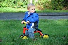 Litet barn med cykeln Arkivbild