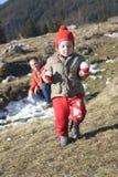 Litet barn med en kasta snöboll Arkivbild
