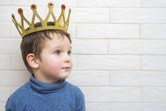 Litet barn med en krona på hans huvud mot en vit tegelstenvägg arkivbild