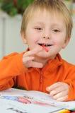 Litet barn med färgpennan i mun Royaltyfria Bilder