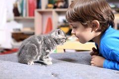 Litet barn med hans kattunge arkivfoto