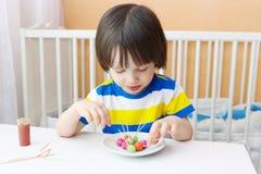Litet barn med klubbor av playdough och tandpetare Fotografering för Bildbyråer