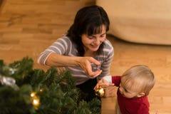 Litet barn med mamman som dekorerar julträdet royaltyfri bild