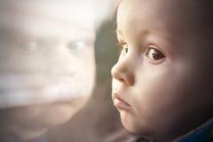 Litet barn med stora ögon i reflexion av fönstret Arkivfoton