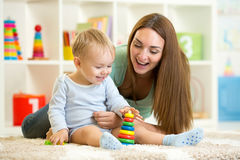 Litet barn och hans mamma som spelar med leksaker Royaltyfria Foton
