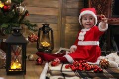 Litet barn och julleksaker arkivfoton