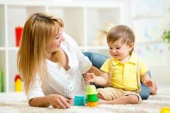 Litet barn och kvinna som spelar med leksaker Royaltyfria Bilder