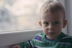 Litet barn på fönstret Arkivfoto