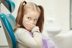 Litet barn på tandläkarekontoret i bekväm stol arkivbild