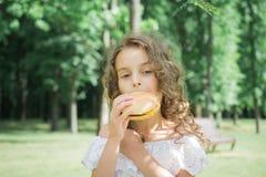 Litet barn som äter en hamburgare eller en ostburgare royaltyfri fotografi