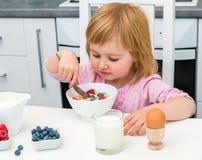 Litet barn som äter mysli Royaltyfri Bild