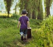 Litet barn som bär en resväska Arkivfoton