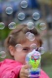 Litet barn som blåser såpbubblor med ett bubblavapen Royaltyfria Bilder