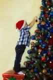 Litet barn som dekorerar julgranen Royaltyfri Bild